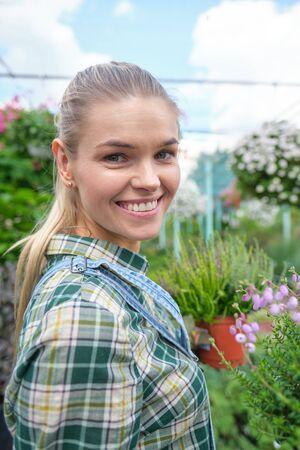 happy  woman gardener choosing flower pot with anthuriums in garden center