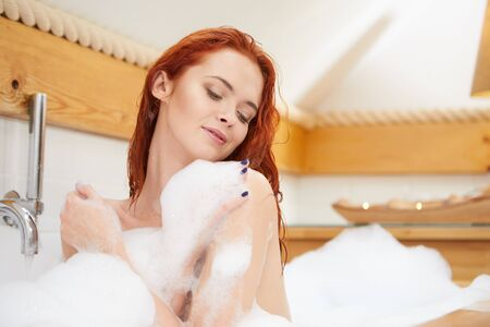 Portrait of redhaired woman playing with foam in bathtub Standard-Bild