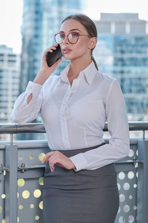 woman manager having phone conversation on the office balcony while drinking her coffee, office routine