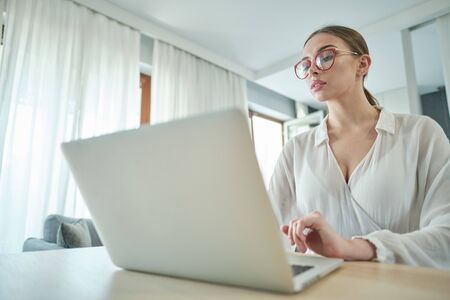 woman in eyeglasses sitting with computer on couch, looking outside, cannot concentrate on work, need some rest, feeling bored, need additional motivation, working remotely at home.