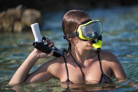 A woman in a bikini hunts with a crossbow