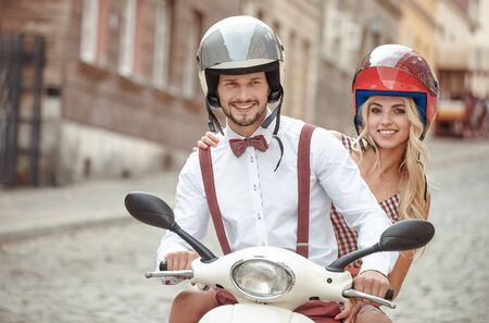 young beautiful hipster couple riding on motorbike city street, summer europe vacation, traveling, romance, Stockfoto