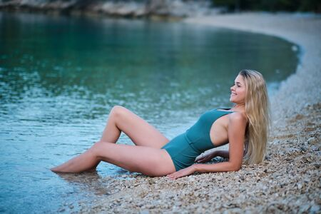 Portrait of beautiful woman on the stones beach. Young caucasian female model on the sea shore.