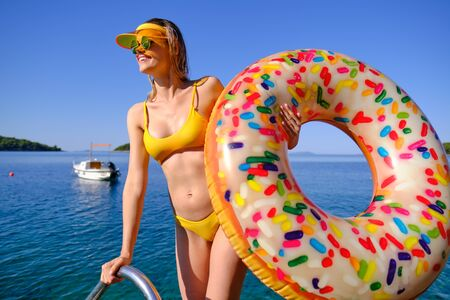 Sunny holiday. Woman with a air donut on the beach