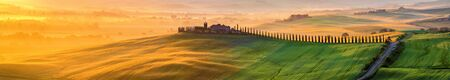 Tuscany landscape at sunrise. Typical for the region tuscan farm house, hills, vineyard. Italy Stock Photo