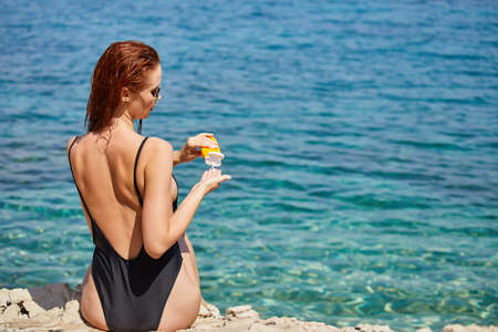Woman applying sunscreen creme on tanned shoulder over the sea
