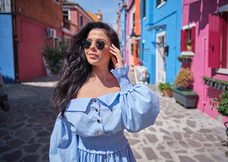 elegant, fashionable girl with glasse stay in the street, in a romantic Burano, Italy