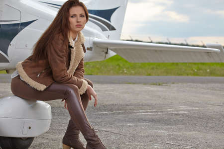 Attractive woman pilot wearing sunglasses standing in the sunshine on an airfield resting against her small private airplane Banque d'images