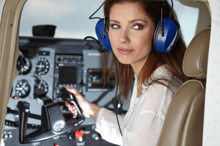 Young Woman Pilot With Headset Looking Through The Cockpit Window. Portrait of attractive young woman pilot with headset. She is looking at camera through the cockpit window of a private plane. Banque d'images