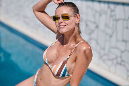 Sexy beautiful brunette woman with sunglasses in bikini relaxing near swimming pool in summer on croatia island in hot weather .Woman relaxing in pool. Foto de archivo