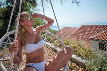 A woman in a bikini sunbaths on a beach in Croatia