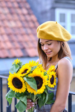 Street portrait of a beautiful young woman holding a sunflower
