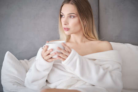 Beautiful Happy Young Woman Drinking Cup Of Coffee Or Tea While Lying In Bed After Waking Up In Morning. Closeup Portrait Of Smiling Girl Enjoying Her Drink While Relaxing At Home.
