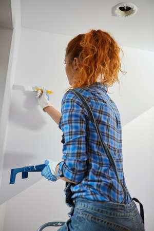 Smiling young woman painting walls in her new house: home renovation and DIY concept Standard-Bild