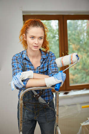 Happy smiling woman doing renovation and painting walls with paint roller