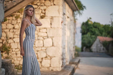 Traveling by Europe. Happy young woman in elegant dress walking by streets, Croatia.