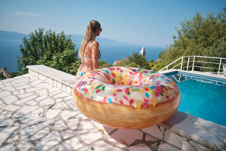 Holiday resort in Croatia. Woman next to swimming pool with sea view. Vacation relax. Sea with mountains at background