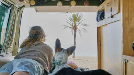 girl and her dog on a bed of a self converted camper van looking through the window living van life Archivio Fotografico