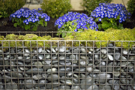 Rock wall supported by wire mesh and topped with moss Stock Photo