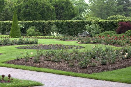 Mooi uitzicht op de tuin met bloemperken, hagen, gras, en het pad