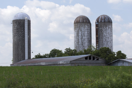 Large silos and farm building with grassy field Stok Fotoğraf