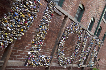 Love spelled out with locks against a brick wall