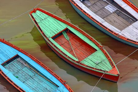 Brightly colored wooden boats on the Holy Ganges River at sunset