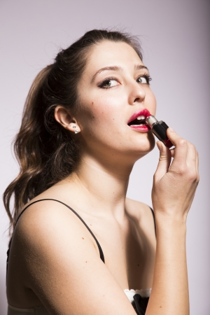 applies: young woman applies eye shadow and lipstick Stock Photo