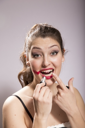 disillusioned: Young woman smears lipstick on her face