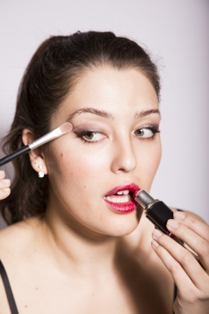 disillusioned: young woman applies eye shadow and lipstick Stock Photo