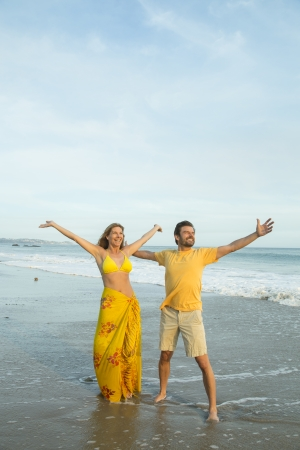 Couple standing on beach with arms outstretched photo