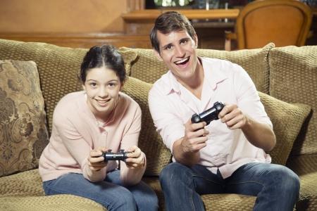 jugando videojuegos: El hermano mayor y una hermana m�s joven jugando juegos de video Foto de archivo