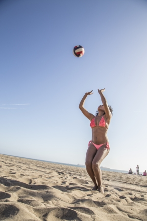 Young woman playing volleyball on the beach photo