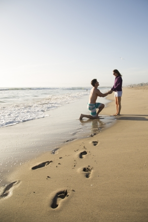 proposes: Young man proposes to woman on the beach Stock Photo