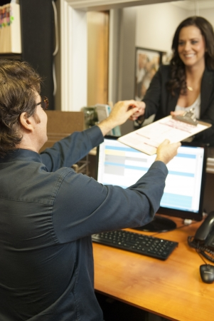 femal: Male receptionist assisting femal patient Stock Photo