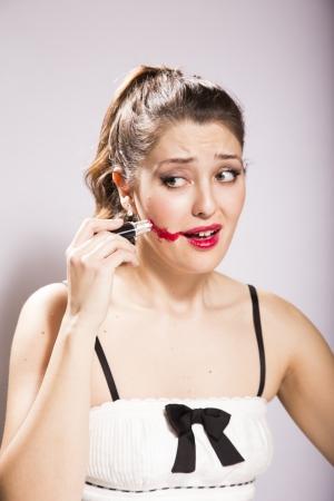 jonge vrouw smeert lippenstift op haar gezicht