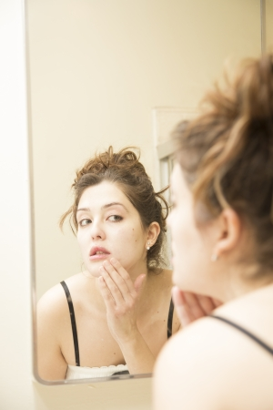 young woman in nightgown looks in mirror