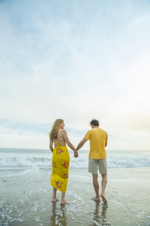Couple holding hands, walking along the beach photo