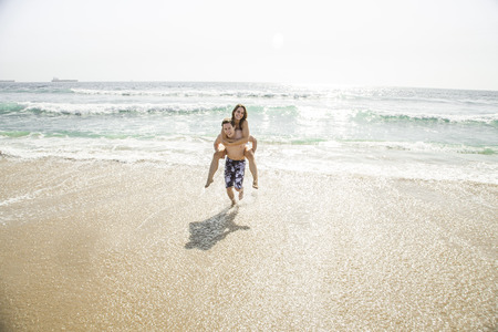 Man giving woman piggy-back ride at the beach Stok Fotoğraf