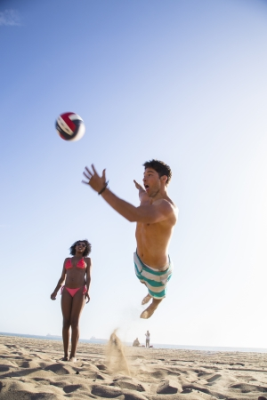 Young man diving for the volleyball photo