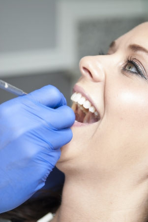 Smiling female dental patient having her mouth examined Stock Photo