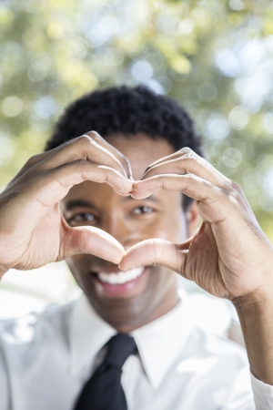 Professional young man folding hands into heart shape photo