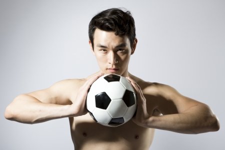 Shirtless athletic male holding soccer ball to chest photo