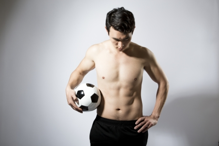 Shirtless athletic male holding soccer ball down at side photo