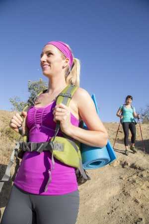 walking pole: Two female hikers coming down the hillside Stock Photo