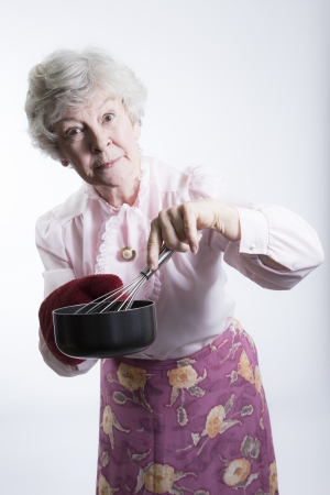 wire whisk: Stern-looking elderly woman with pot and wire whisk