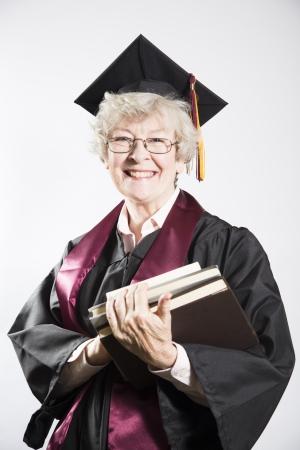 alumni: Graduado de la universidad mayor que sostiene los libros Foto de archivo
