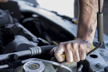 male mechanic working on car
