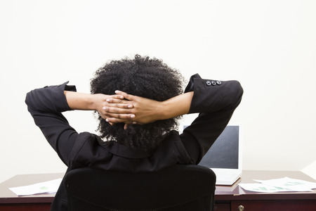 relieved: african american woman relaxing at desk