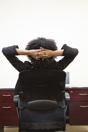 easy going: african american woman relaxing at desk